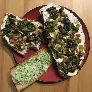 Three pieces of bread on a red plate. One has butter flecked with green bits of watercress. The other two have a layer of creamy white ricotta festooned with an untidy mix of dark green sautéed ramps, golden raisins and pine nuts.