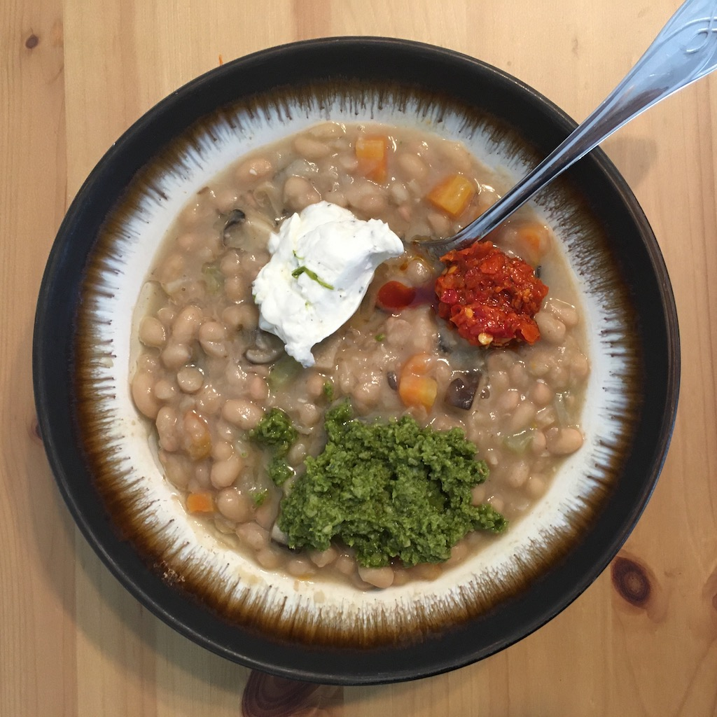 A bowl of white beans, unremarkable except for a blob of white ricotta cheese, green pesto and red pepper sauce on top.