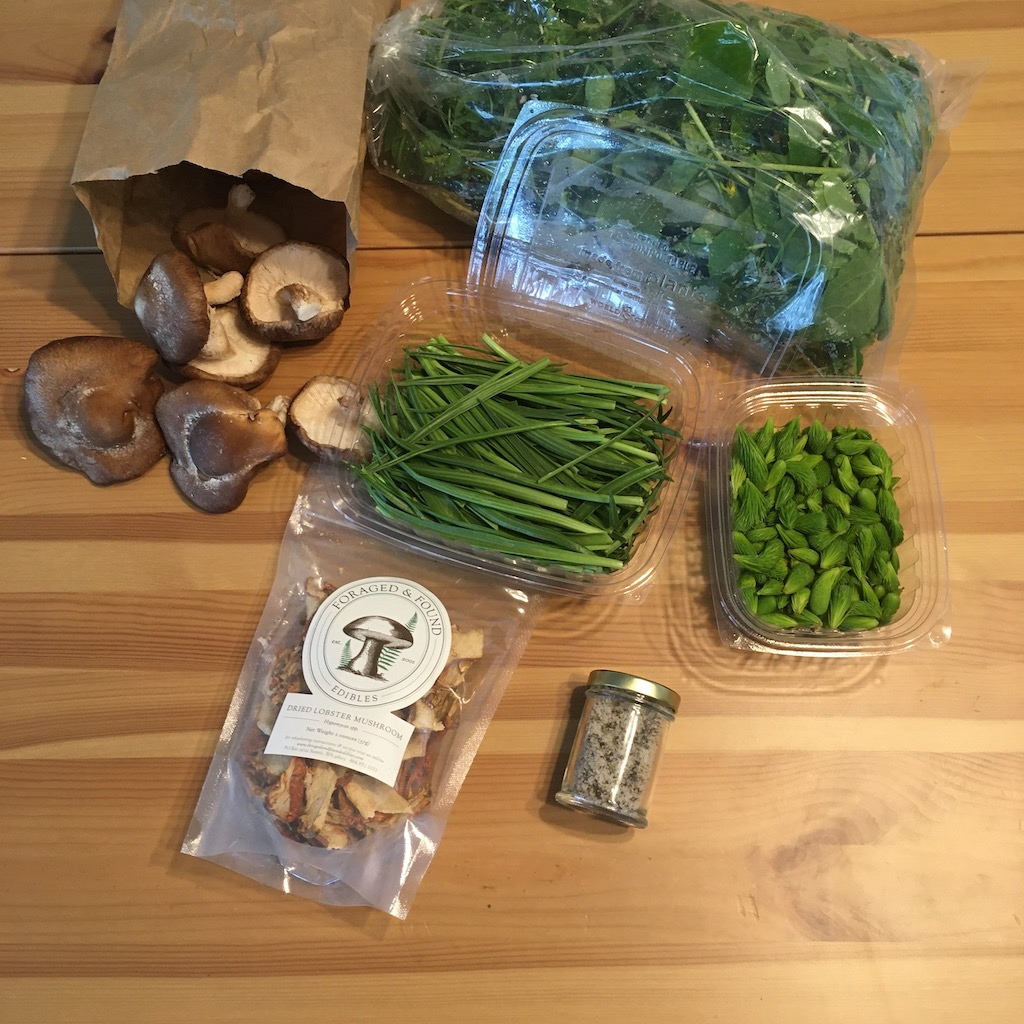 A variety of food laid out on a table: a paper bag with some extremely normal mushrooms spilling out of it, a plastic bag with some green leafy stuff with visible stems, two plastic containers one of which contains small spiky green plant bits and the other of which contains what looks like thick blades of grass, a small jar of grayish mottled powder, and a sealable plastic bag with dried mushrooms.